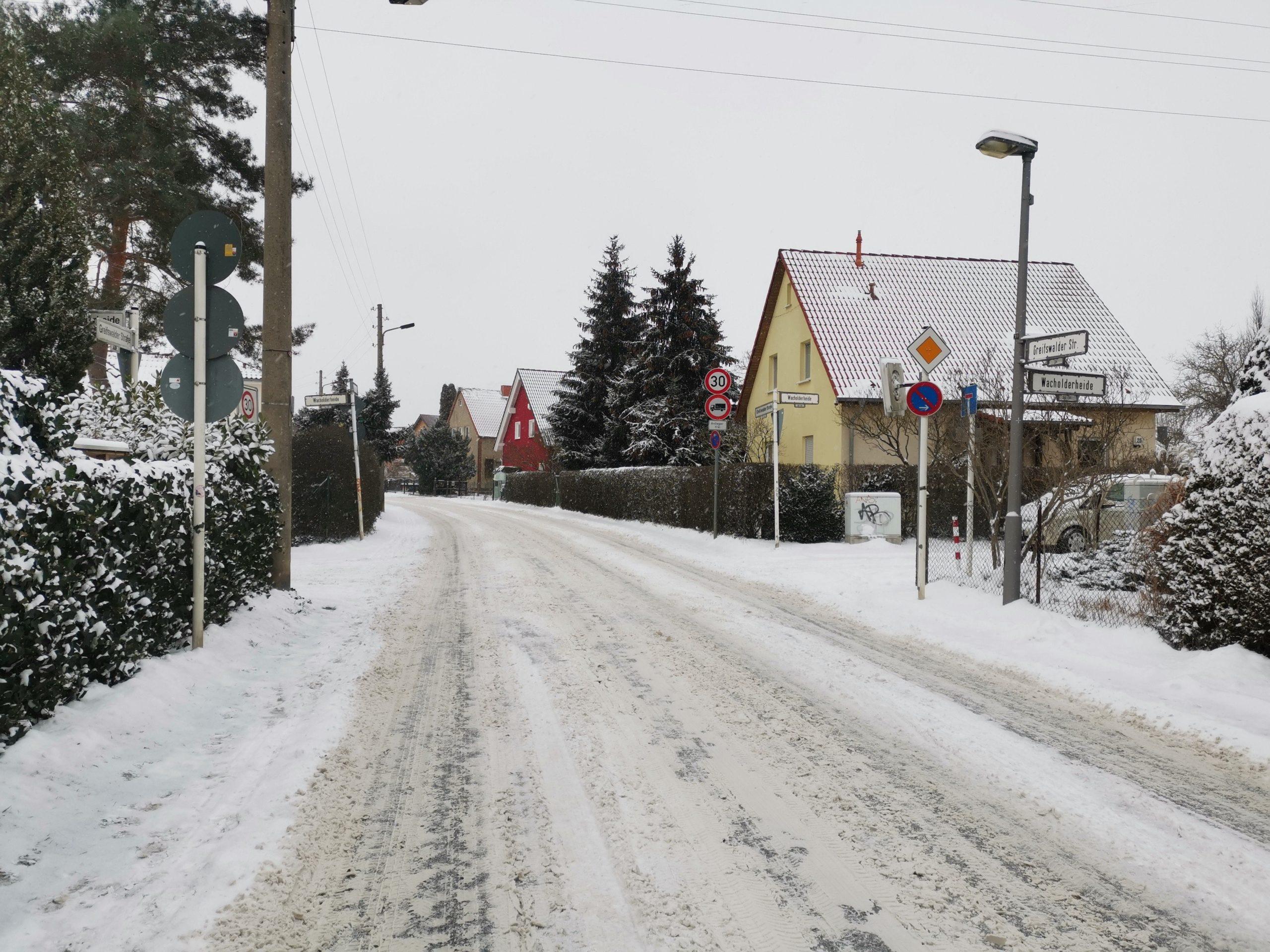 Foto von einer verschneiten Kreuzung: Greifswalder Straße Ecke Hermelinstraße. Die Fußwege sind sehr schmal und nicht geräumt.