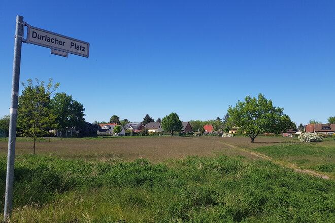 """Ein Foto des Straßenschilds """"Durlacher Platz"""" - auf den sonnenbeschienenen, aber brachliegenden Platz zeigend.."""